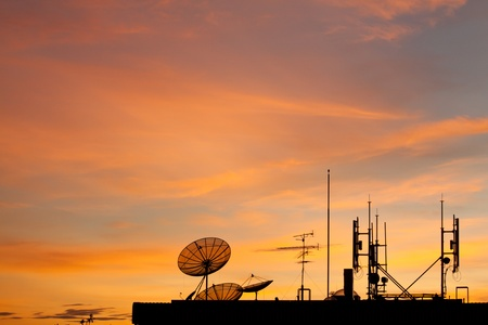 radio station: Worldwide Communication,  Satellite and other antenna network against beautiful sky at sunset, silhouette style