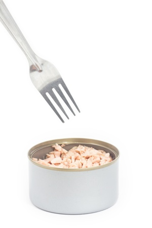 Tuna in vegetable oil with fork on white photo