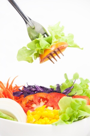 Vegetables Salad in white bowl with some on fork photo