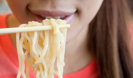 Noodle on chopsticks with woman in the background, Shallow depth of field Stock Photo - 11963243