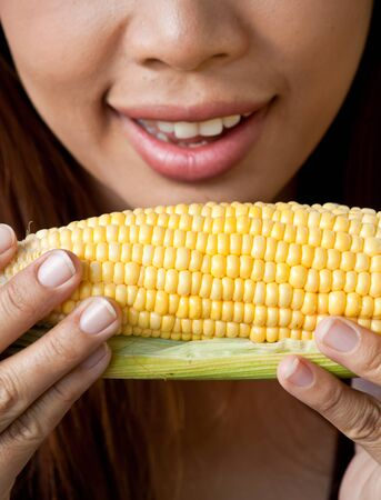 Young woman going to eat fresh yellow corn Stock Photo - 13219788