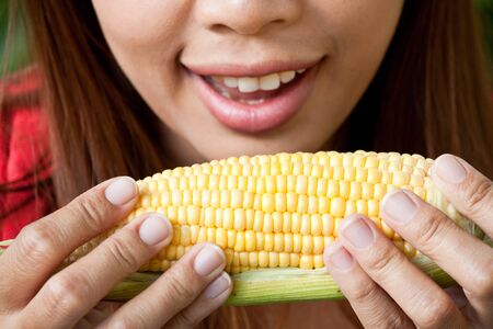 Young woman going to eat fresh yellow corn Stock Photo - 13382409
