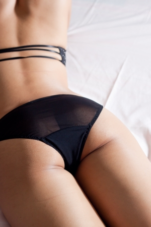 Sexy female buttom in black lingerie in bed Stock Photo