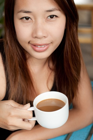 Young girl holding a cup of coffee photo