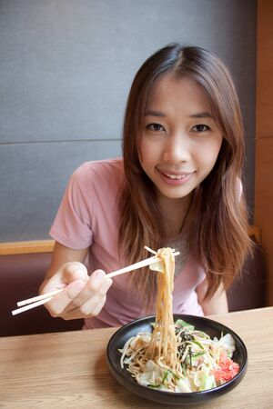 Asian young girl eating japanese noodle style with chopsticks photo
