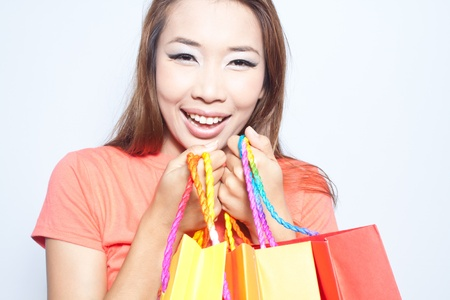 Asian woman smiling and holding colorful shopping bags Stock Photo - 14451511