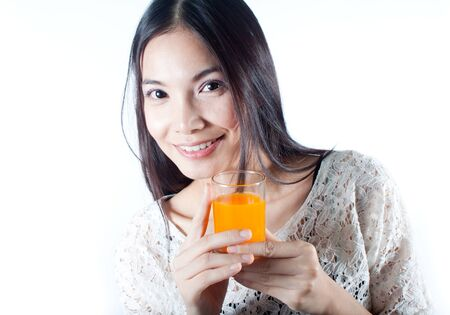 Healthy woman smiling and holding a glass of orange juice Stock Photo - 15003061