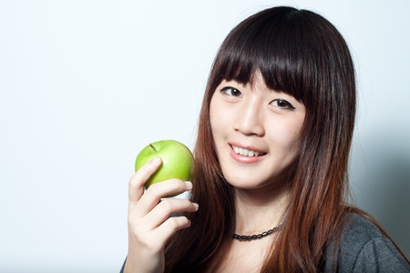 Young girl holding green apple  and smiling Stock Photo - 15166127