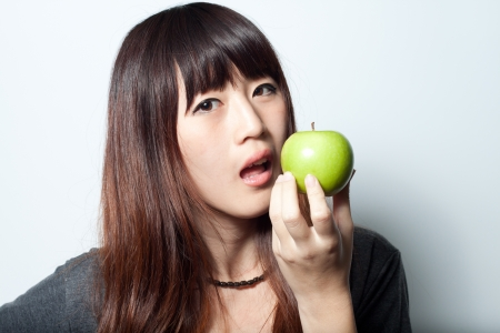 Young girl going to  eat green apple photo