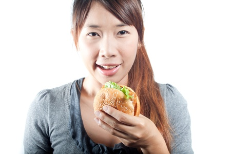 Cute young woman with fish burger in   her hand on  white background photo