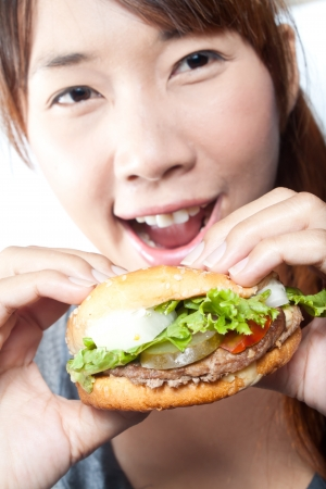 Young woman going to eat burger, shallow  depth of field,  focus at a burger photo