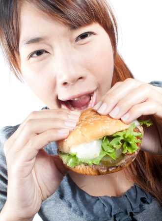 Young woman going to eat burger, shallow  depth of field,  focus at woman photo