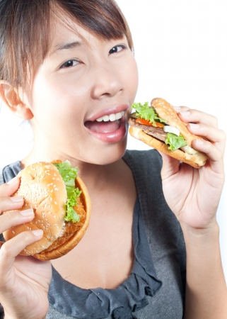 Young woman going to eat two burgers  in her hand on white background photo