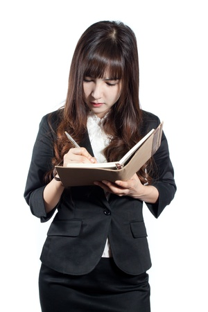 Portrait of young business woman holding a notebook and writing something photo