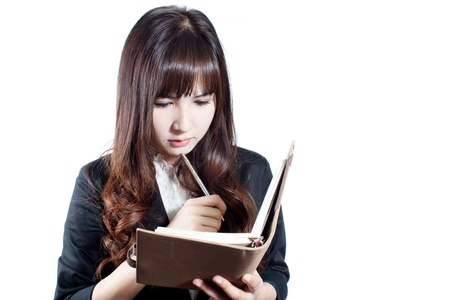 Portrait of young business woman holding a notebook and thinking on white background photo