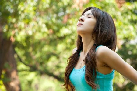 aire puro: Mujer joven que toma una respiración profunda, disfrutando del aire fresco en verde parque Foto de archivo