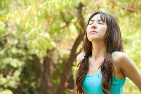 Young woman taking a deep breath, enjoying fresh air in green park Stock Photo