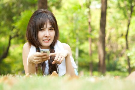 Young happy woman playing with her mobile while lying on the green grass at park photo