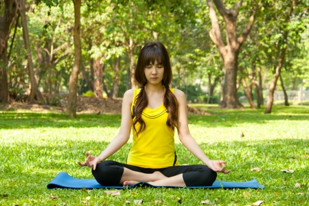 Beautiful young asian woman doing yoga on green grass at park photo
