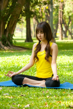 Beautiful young asian woman doing yoga on green grass at peaceful park photo