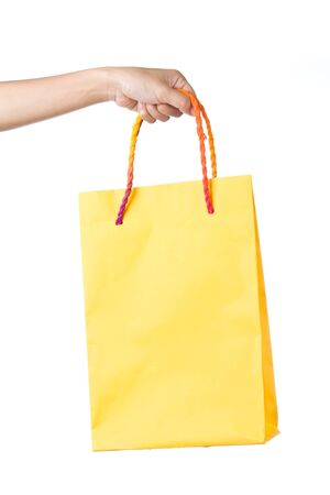 Lady hand holding yellow paper shopping  bag with  beautiful  color rope handle on white background Stock Photo - 17451979