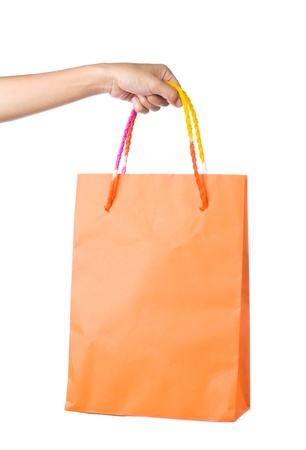 Lady hand holding orange paper shopping  bag on white background Stock Photo - 17451992