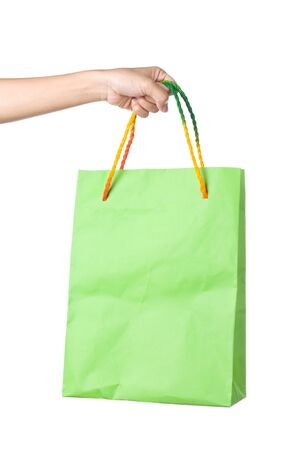 Lady hand holding green paper shopping  bag with  beautiful  color rope handle on white background Stock Photo - 17451995