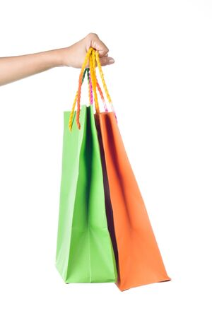 Lady hand holding orange and green paper shopping  bag with  beautiful  color rope handle on white background Stock Photo - 17451990