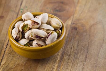 frutas secas: Tuerca de pistacho en tazón en la mesa de madera Foto de archivo