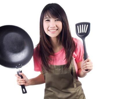 Young asian woman housewife with pan and  apron on white background photo