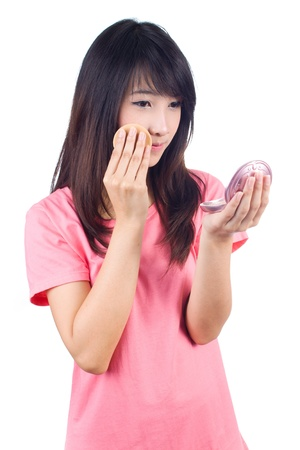 Portrait of the beautiful young asianwoman applying makeup on white background photo