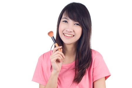 Portrait of beautiful asian woman in casual clothes with makeup brushes on white background photo