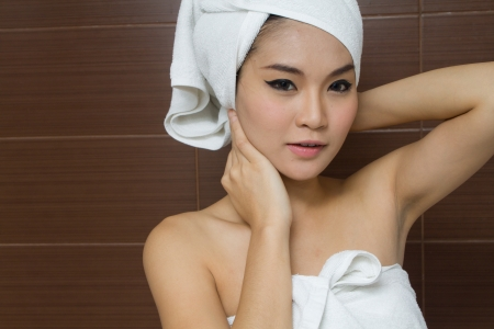 woman in towel: Beautiful woman wearing white towel in the bathroom Stock Photo