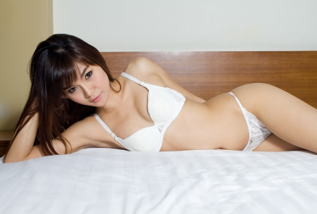 Sexy asian woman in white sexy lingerie lying  in her bed
