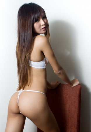 Sexy asian woman in white sexy lingerie on red chair
