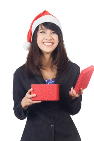 Young excited asian  business  woman with santa hat open a red  gift box on white background photo