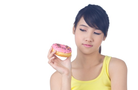 Young cheerful asian girl smiling  with donut in her  hand  white background photo