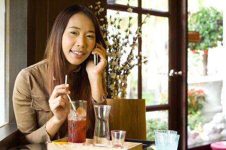 Young happy asian woman talking on cellphone  in the restaurant photo