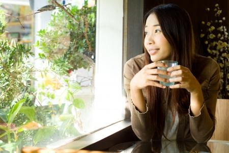 hot asian: Юная красавица женщина, глядя из окна и проведение стакан воды в ресторане