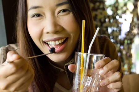 Young beauty woman smiling  and holding a glass of water in the restaurant photo