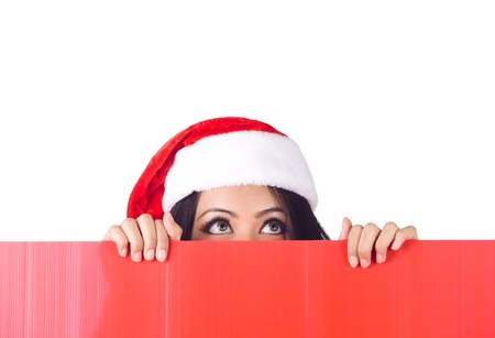 Christmas woman peeking over edge of red billboard and lokking up with copy space photo