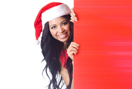 Christmas woman peeking over edge of red billboard with copy space photo