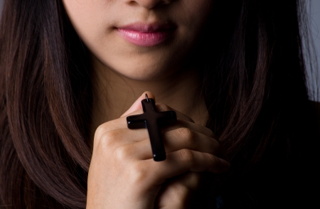 Young woman  praying with rosary in hand photo