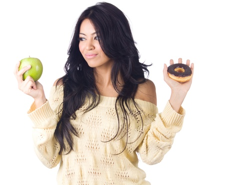 confused woman: Diet woman holding apple and donut on white background