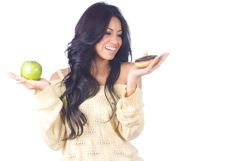 Diet woman holding apple and donut on white background photo