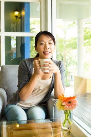 Young woman drinking  hot coffee in sidewalk cafe photo