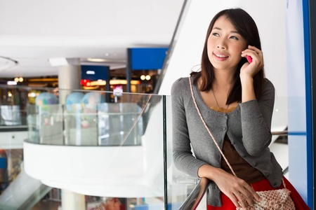 Young woman talking on mobile phone  in shopping mall photo