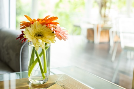 Vase full of  colourful flowers on glass table with sofa at Cafe photo