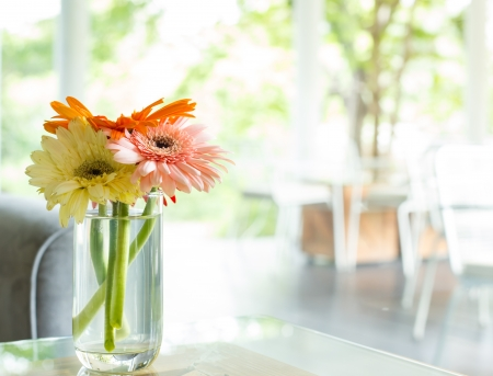 Vase full of  colourful flowers on glass table with sofa at Cafe