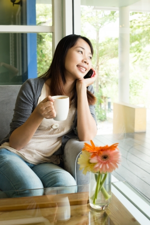 Young woman drinking  hot coffee and talking on phone in  sidewalk cafe photo